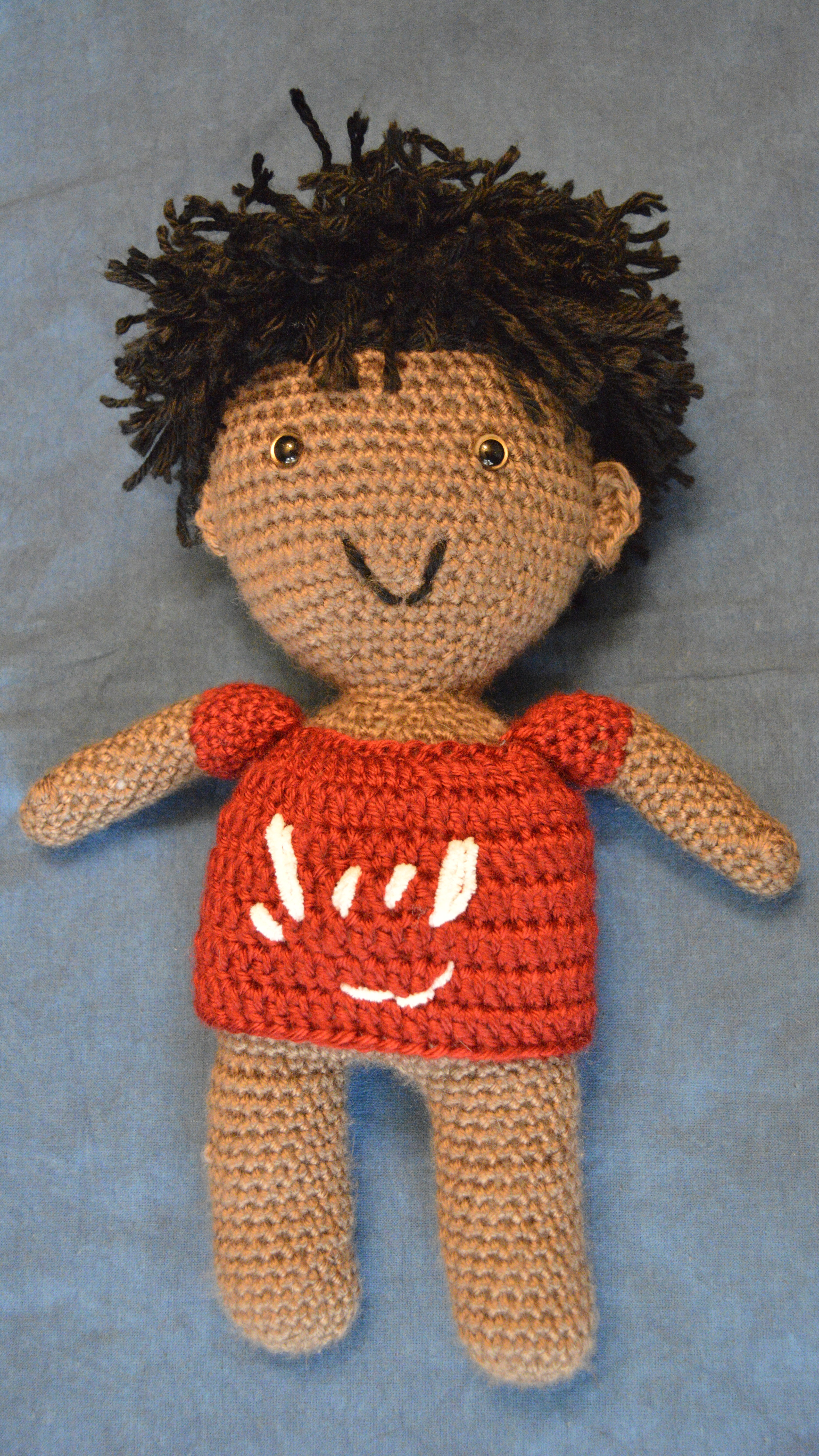 medium-skinned deaf boy doll with one microtia ear, shaggy black hair and red shirt with ILY; plush deaf dolls with hearing aids and cochlear implants