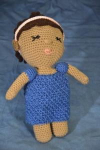 medium-skinned brunettedeaf  doll with softband baha hearing aid and blue dress