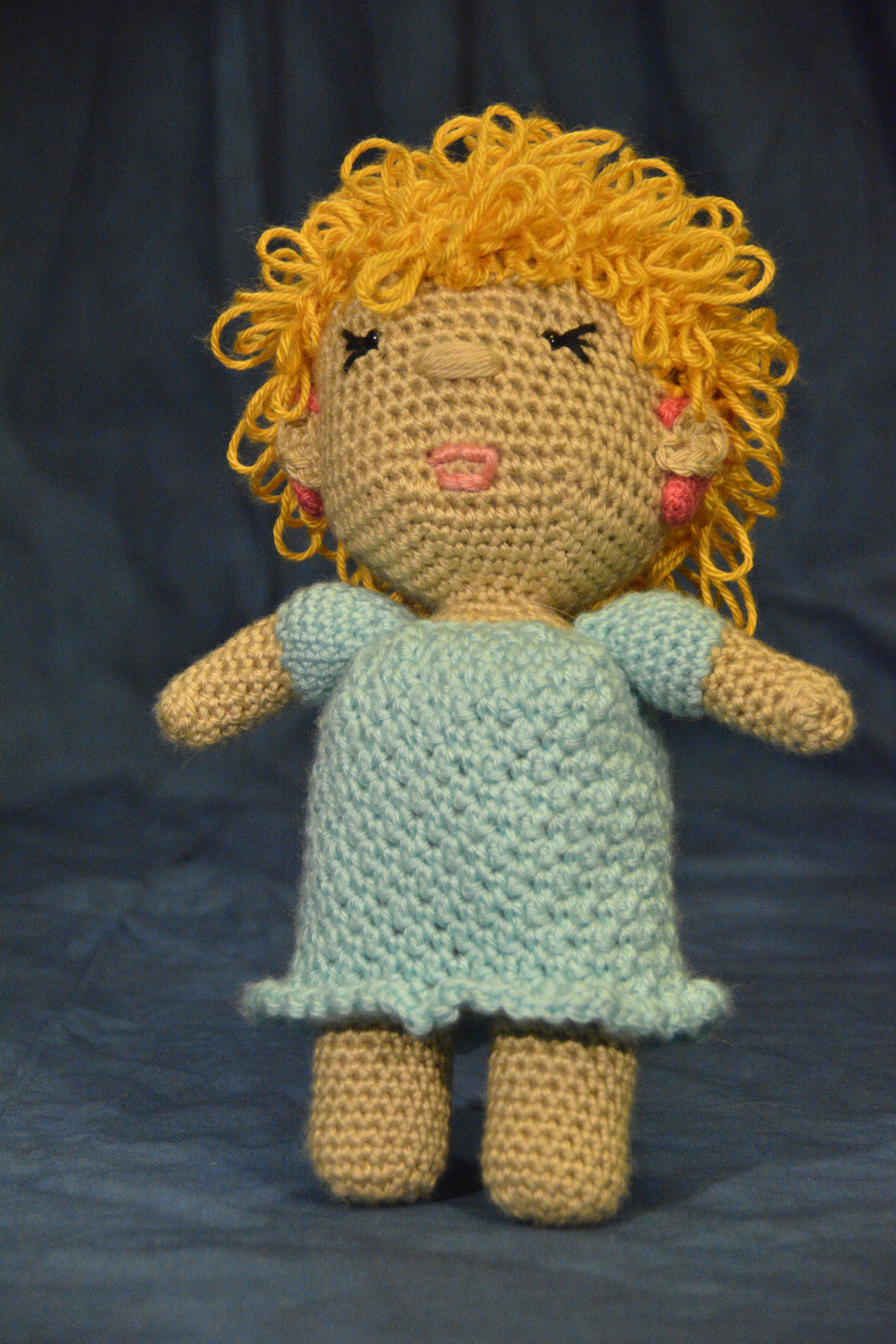 blonde caucasian deaf doll with pink cochlear implants and light blue dress