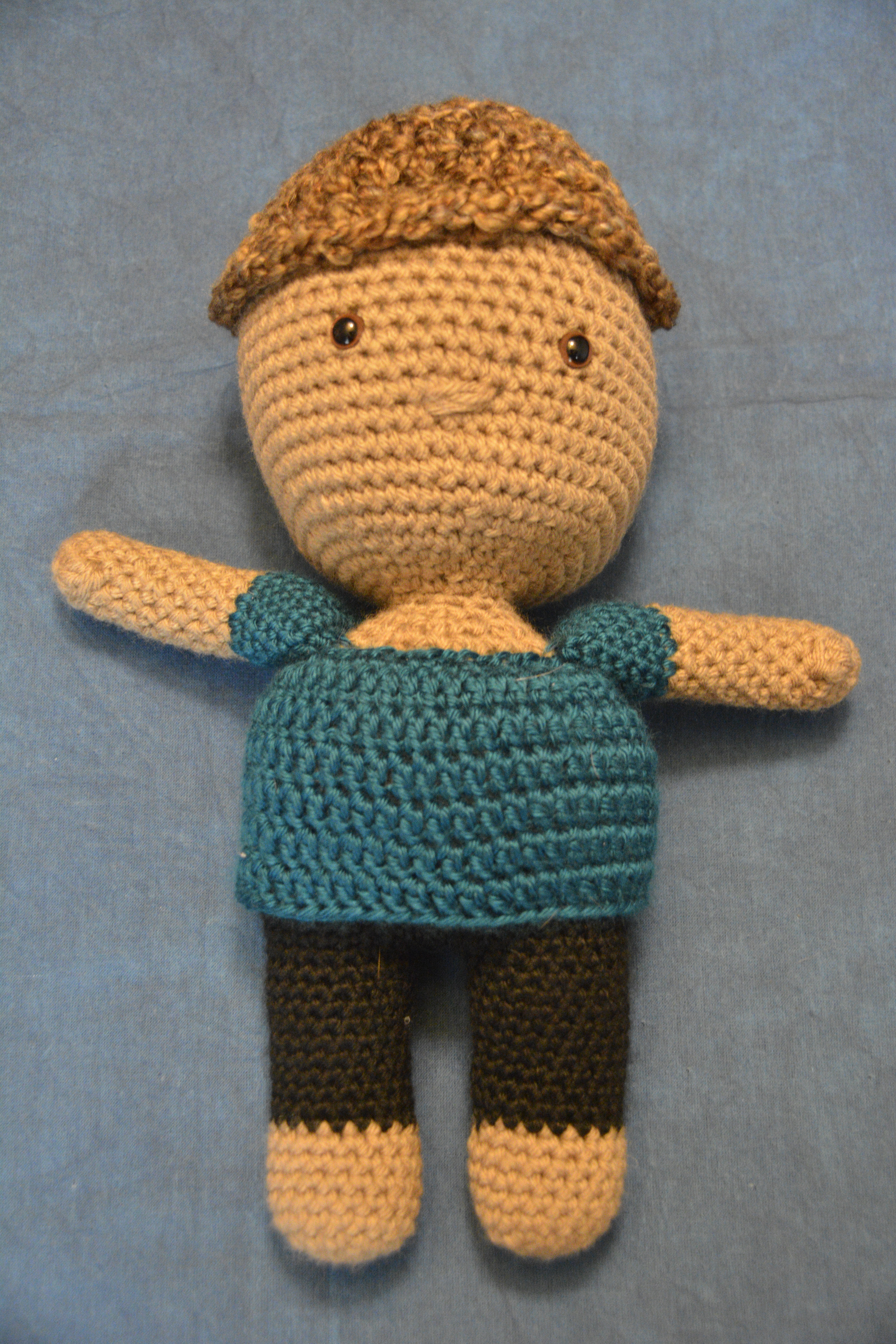 tan deaf boy doll with short hair, no ears, turquoise shirt, and black pants; plush deaf dolls with hearing aids and cochlear implants