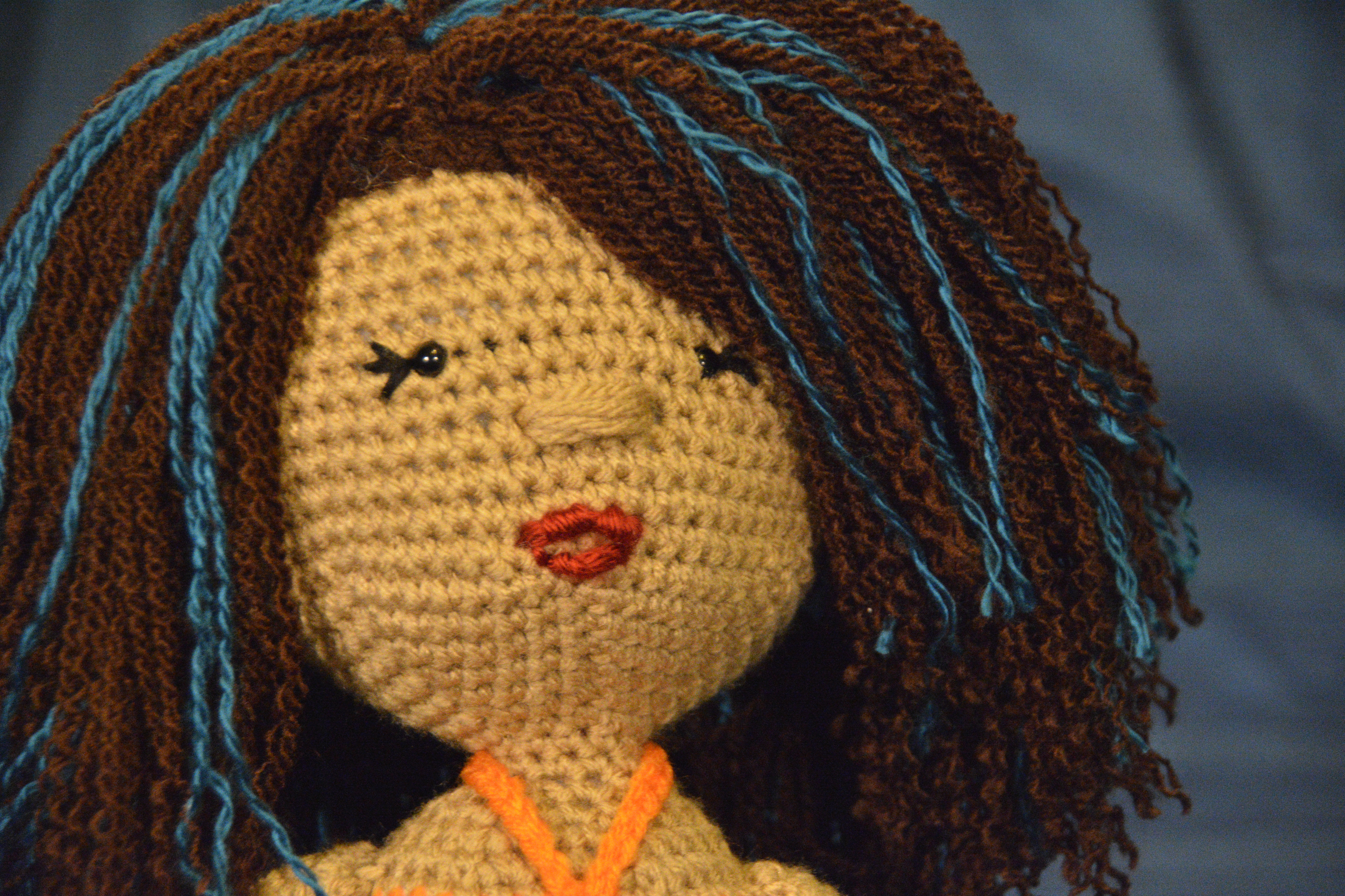 tan-skinned deaf doll with dark brown wavy hair with teal streaks; plush deaf dolls with hearing aids and cochlear implants