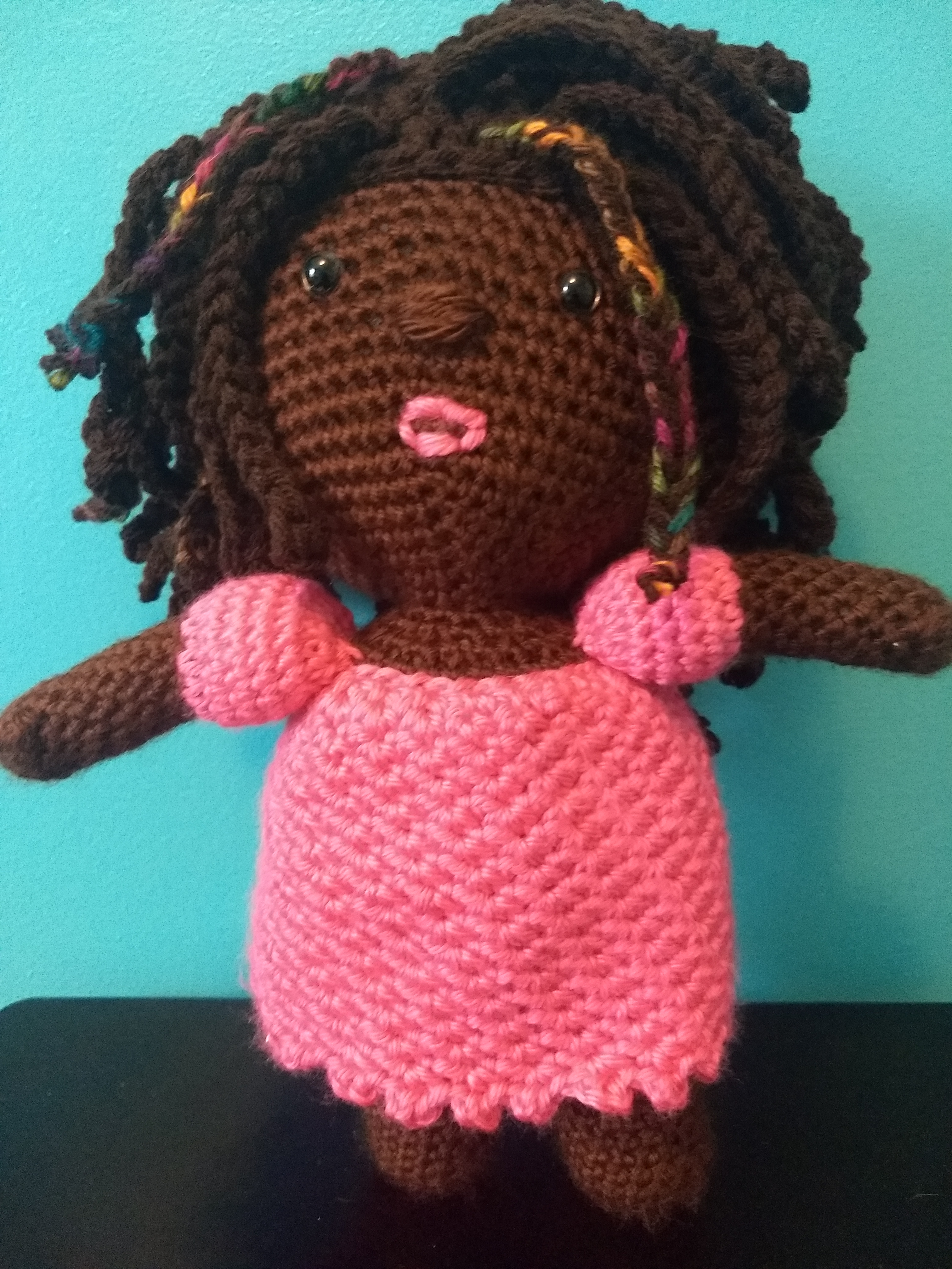 handmade deaf doll with chocolate skin, braids, and hot pink dress; plush deaf dolls with hearing aids and cochlear implants